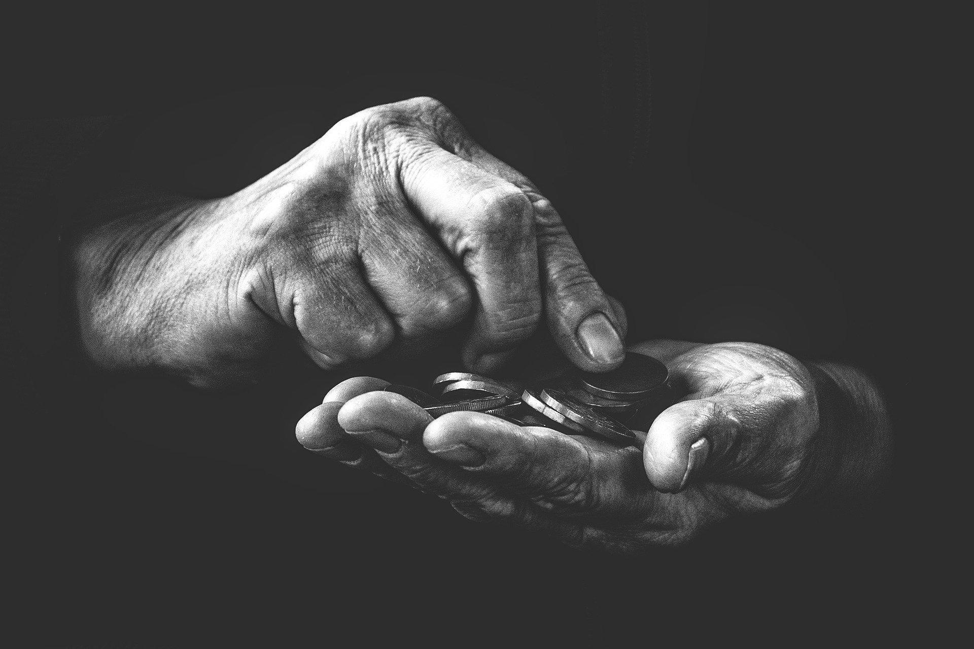 Sort-hvid hænder holder mønter